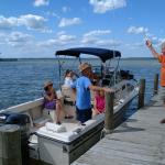 family in boat at dock