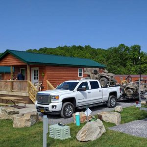 Cabin with truck in parking area with ATVs on trailer