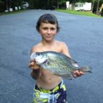 young boy holding fish
