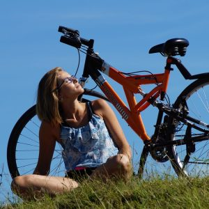 woman with bike sitting in grass