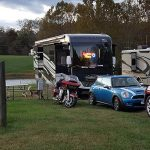 rvs in grass with cars and motorcycle