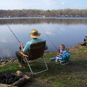 toddler and man sitting in chairs fishing