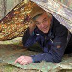 man laying under tarp