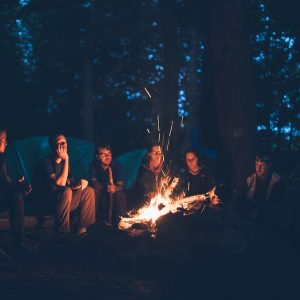 adults sitting around campfire