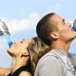 man and woman drinking from water bottles