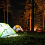 tent camping with bonfire in the trees